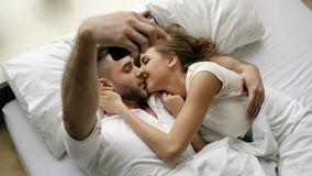 Young beautiful and loving couple take selfie picture on smartphone camera and kiss while lying in bed at the morning. Young beautiful and loving couple take stock image