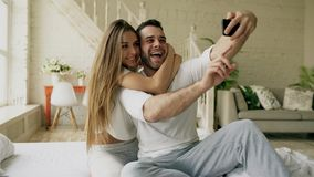 Young beautiful and loving couple take selfie picture on smartphone camera while sitting in bed at the morning. Young beautiful and loving couple take selfie royalty free stock photography