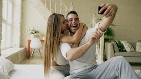 Young beautiful and loving couple take selfie picture on smartphone camera while sitting in bed at the morning. Young beautiful and loving couple take selfie stock images