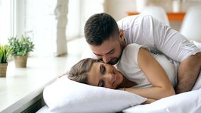 Young beautiful and loving couple wake up at the morning. Attractive man kiss and hug his wife in bed. Young beautiful and loving couple wake up at morning Royalty Free Stock Photo