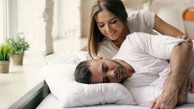 Young beautiful and loving couple wake up at the morning. Attractive woman kiss and hug his husband in bed Stock Photo