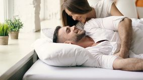 Young beautiful and loving couple wake up at the morning. Attractive woman kiss and hug his husband in bed. Young beautiful and loving couple wake up at morning royalty free stock photography