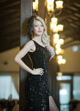 Young beautiful luxurious woman in long elegant black dress. Beautiful young blonde woman with bright lights in background Royalty Free Stock Image
