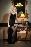 Young beautiful luxurious woman in long elegant black dress. Beautiful young blonde woman with bright lights in background. Seductive blonde woman in luxury stock image