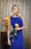 Young beautiful luxurious woman in long elegant blue dress holding an yellow flower. Beautiful young blonde woman with curtains Stock Photos