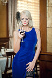 Young beautiful luxurious woman in long elegant dress. Beautiful young blonde woman in blue dress holding a glass of wine royalty free stock image