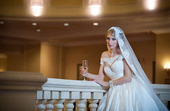 Young beautiful luxurious woman in wedding dress posing in luxurious interior. Bride with huge wedding dress in majestic manor Royalty Free Stock Images
