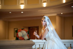 Young beautiful luxurious woman in wedding dress posing in luxurious interior. Bride with huge wedding dress in majestic manor. Seductive blonde bride with stock image
