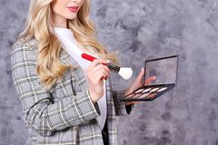 Professional visagiste posing with her equipment over grunged concrete wall background. Young beautiful makeup artist w/ long curly hair wearing fashionable stock image