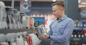 Young beautiful man chooses an electric kettle to buy. Holds a device in his hands, studies the price tags and the. Characteristics and design of the model stock video