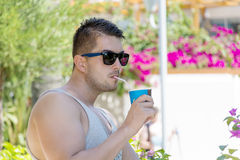 Young beautiful man drinking cocktail in a tropical garden Stock Image