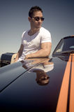 Young beautiful man leaning against muscle car. With orange stripes Stock Photography