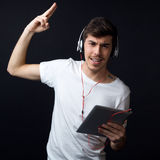 Young beautiful man listening to music. Isolated on black. Stock Photography
