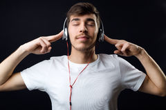 Young beautiful man listening to music. Isolated on black. Royalty Free Stock Photos