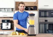 Young beautiful man is making a smoothy with a mixer stock image