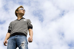 Young beautiful man model standing under the cloud. Y sky. Blue cloudy sky background Royalty Free Stock Photography