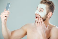 Young and beautiful man with Purifying Mask on his face doing selfie.  royalty free stock photo