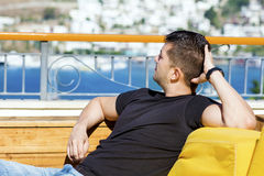 Young beautiful man relaxing and looking the blue sea. Young beautiful man relaxing outdoor and looking the sea stock photo