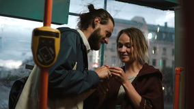 Young beautiful man and woman feeding each other the candies or sweets, having fun. Happy couple in tram. stock footage