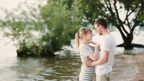 Young beautiful man and woman standing on the beach and talking. Happy couple hugging on the shore of the river. stock footage