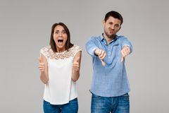 Young beautiful married couple posing over grey background. Royalty Free Stock Photography