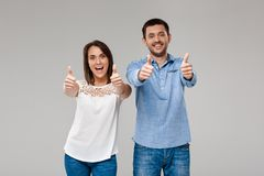 Young beautiful married couple posing, showing okay over grey background. Stock Photo