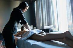 Young beautiful massage therapist massaging client with beautifu Stock Image