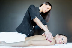 Young beautiful massage therapist massaging a stunning young lad Royalty Free Stock Photo
