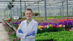 Young beautiful middle-aged woman in glasses, a white coat and blue rubber gloves, a scientist agronomist, posing with stock footage