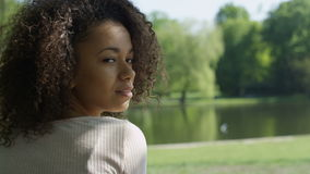 Young beautiful mixed race woman with curly afro hair smiling happily in a green park.