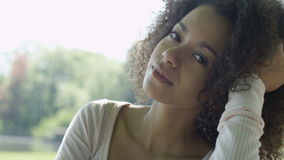 Young beautiful mixed race woman with curly afro hair smiling happily in a green park. stock footage
