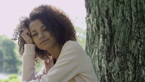 Young beautiful mixed race woman with curly afro hair smiling happily in a green park. stock video