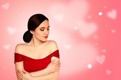 Young Beautiful Model Girl in Red Dress on Light Pink Background with Hearts. Concept Valentine`s Day. Holiday Card. Stock Photography