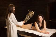 Young beautiful model girls on wooden loungers relaxing in a sauna. Beauty and wellness lifestyle stock photo