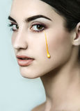 Young  beautiful model with golden tears. Stock Image