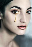 Young  beautiful model with golden tears. Royalty Free Stock Photography