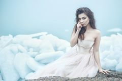 Young beautiful model in luxurious strapless corset ball gown sitting on slabs of broken ice at the misty seaside royalty free stock photo