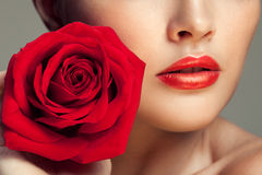 Young beautiful model with red rose near lips Royalty Free Stock Photo
