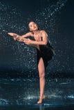 The young beautiful modern dancer dancing under water drops. In blue aqua studio stock images