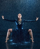 The young beautiful modern dancer dancing under water drops Stock Photos