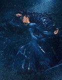 The young beautiful modern dancer dancing under water drops. The young beautiful modern dancer in long dress dancing under water drops in blue aqua studio royalty free stock image