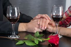 Couple hands on restaurant table with two glasses of red wine and roses. Young beautiful modern hands on restaurant table with two glasses of red wine and roses stock image