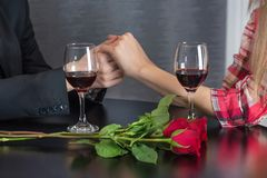 Man holding hands of girl on restaurant table with two red wine glasses and red roses flower stock photography