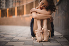 Young beautiful modern style ballet dancer sitting on the ground in black dress . selective focus. Stock Photo