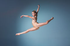 Young beautiful modern style dancer jumping on a studio background Stock Photography