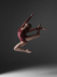 Young beautiful modern style dancer jumping on a. Studio gray background Stock Photo