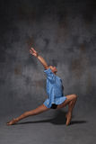 Young beautiful modern style dancer posing on a. The young beautiful modern style dancer in a blue shirt posing on a studio gray background Royalty Free Stock Image