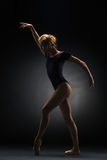 Young beautiful modern style dancer posing on a studio background. Young beautiful modern style dancer posing on a studio dark background royalty free stock photos