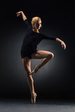 Young beautiful modern style dancer posing on a studio background Stock Photos