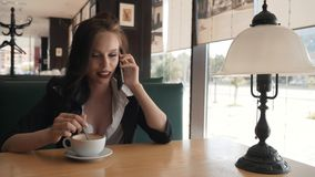 Young beautiful modern woman speaks with a girlfriend on the phone. A girl is resting in a cafe, talking on the phone. Young beautiful modern woman speaks with stock footage
